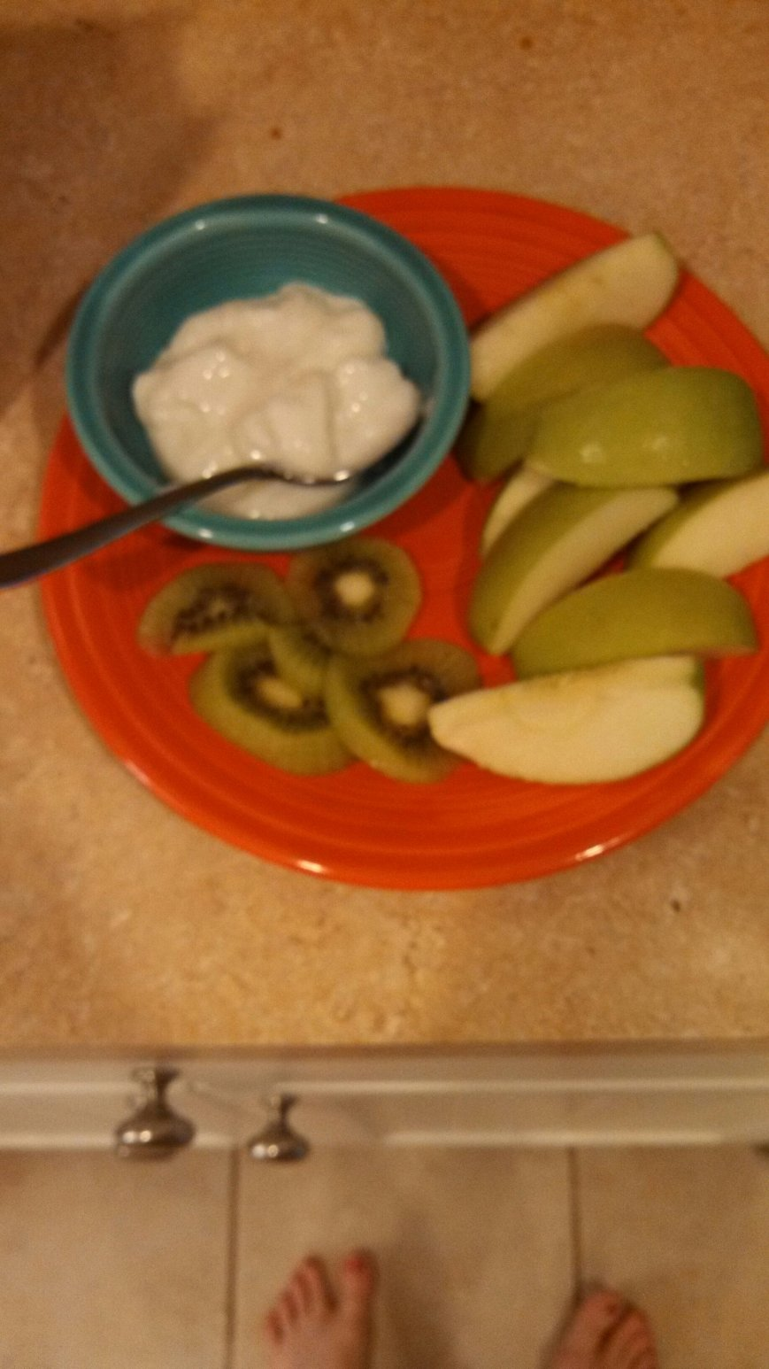 A sliced apple, plain yogurt, and a sliced kiwi.